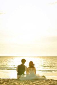 砂浜に座って海を眺める背中
