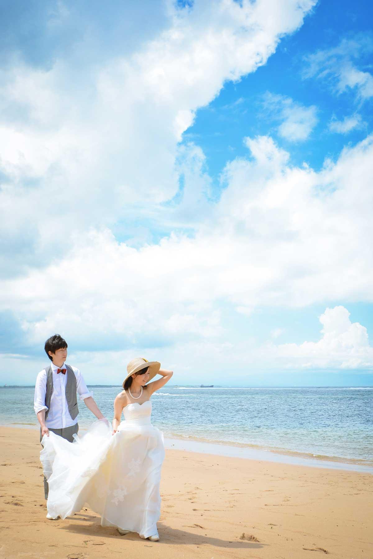 ドレスの裾を持って歩く新郎新婦 - タイチ撮影