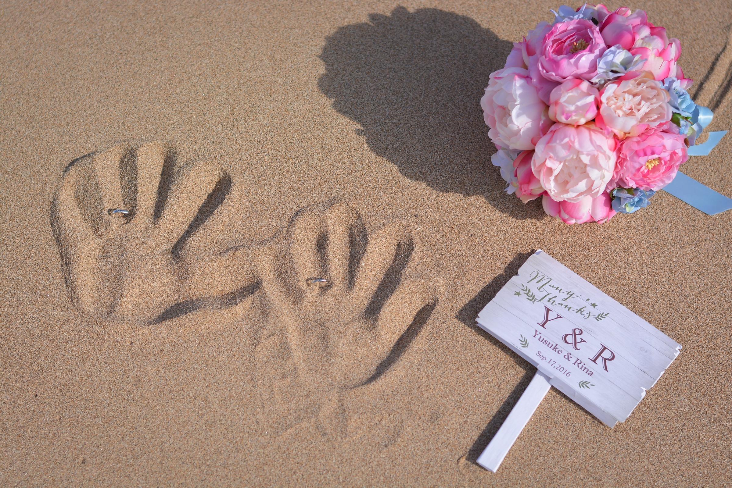砂に手形と指輪をさして