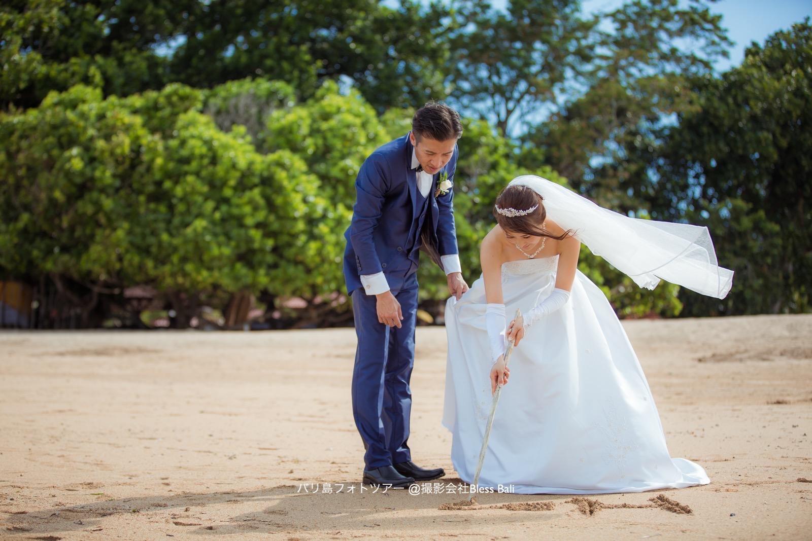 砂浜に文字を書く新郎新婦
