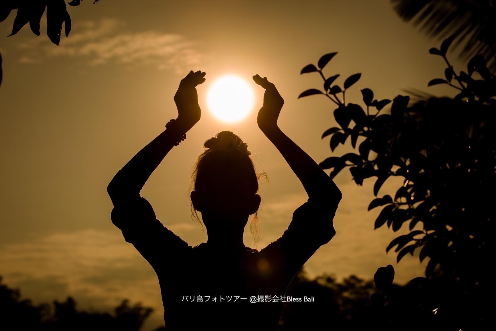 サンセットの太陽を手で包んだ幻想的なショット